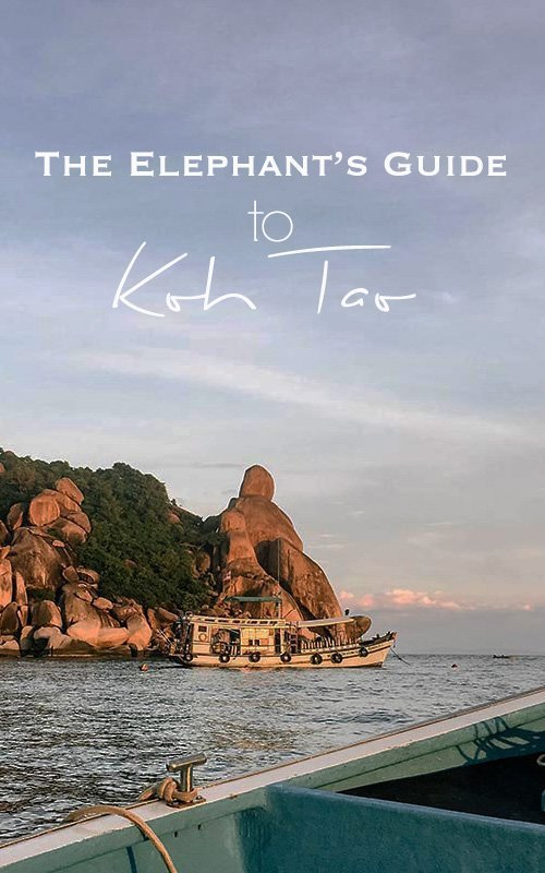 Sunset on the ocean taken from a wooden boat with view of boulders and a dive boat with text overlay - The Elephant's Guide to Koh Tao
