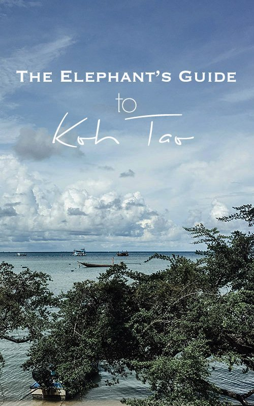 Ocean view with lots of greenery in the foreground and white clouds on the blue sky with text overlay - The Elephant's Guide to Koh Tao