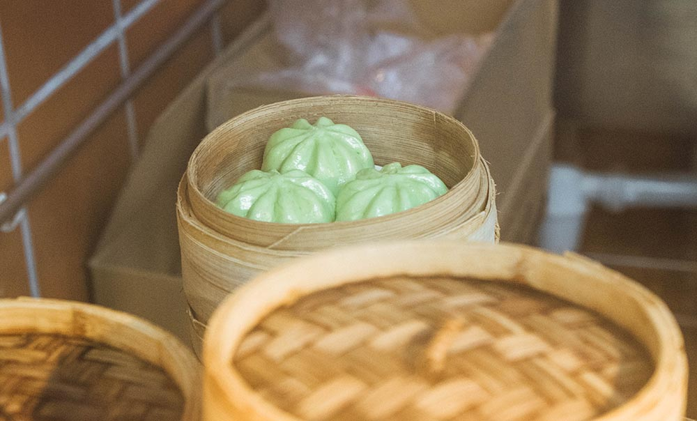 Green steamed dumplings in a bamboo steamer