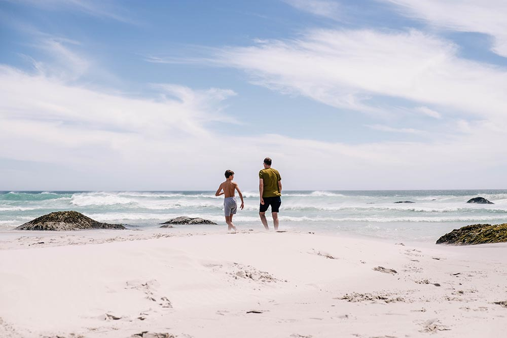 Father and son walking towards the ocean on Noordhoek beach in Cape Town.