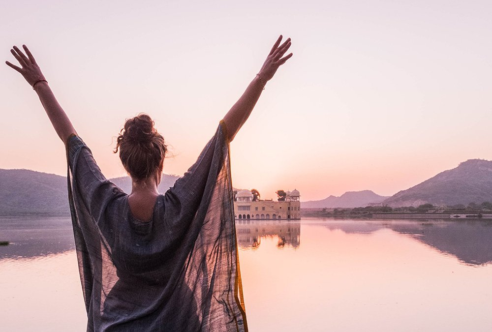 Woman greeting the Sunrise over the Jal Mahal in Jaipur