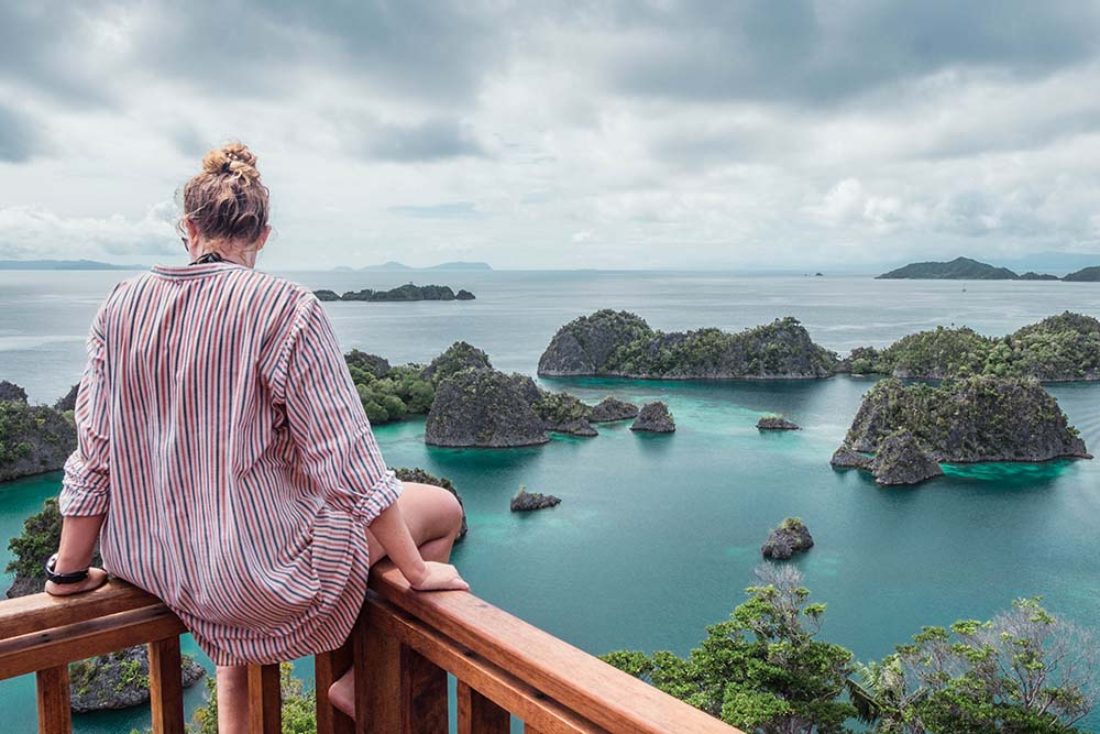 Woman sitting on railing overlooking islands in Raja Ampat