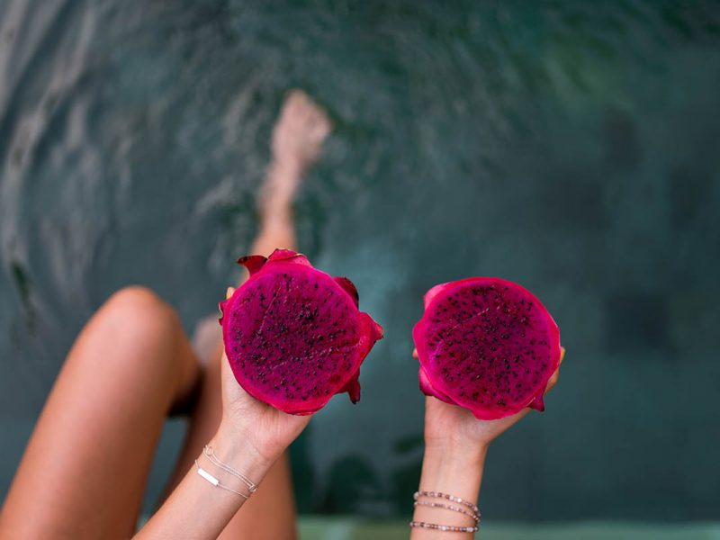Hands holding pink dragonfruit halves over water